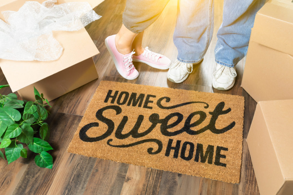 Blog - Man and Woman Standing Near Home Sweet Home Welcome Mat, Moving Boxes and Plant.